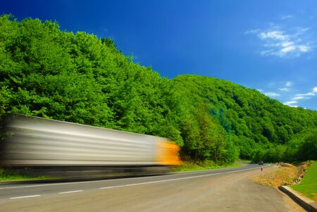Heavy truck on the road. Motion blur. Deep blue sky