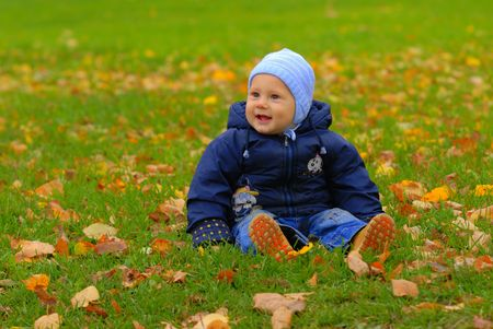 Little cute kid playing on autumn meadow