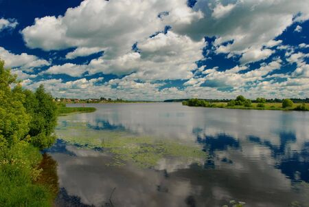 Idyllic river landscape. Summertime, clouds