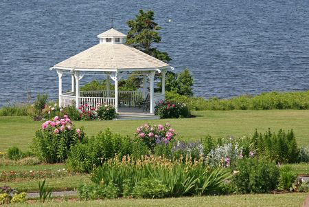A pretty  gazebo surrounded by peonies in a seaside garden.