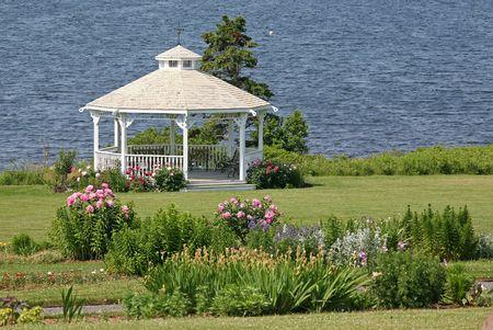 A pretty  gazebo surrounded by peonies in a seaside garden.