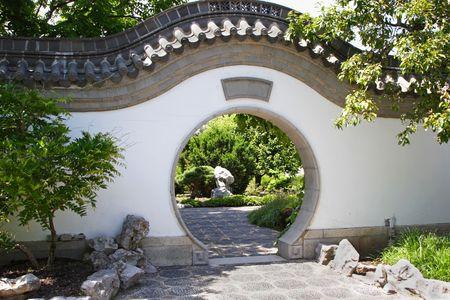 A circular gate to a lush oriental garden.