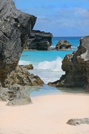 A secluded pink beach and turquoise ocean on the shoreline of Bermuda.