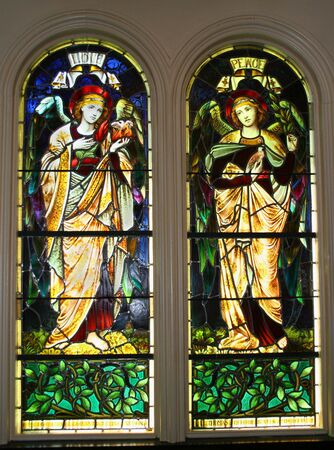A pair of old stained glass windows circa 1899 showing two angels, labeled as  and Peace. Stock Photo - 3303345