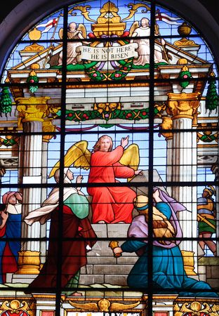 A stained glass window featuring a red angel from an Anglican church in St. Vincent with the inscription 'He is not here He is risen'. Note that there is a wire grate on the other side of the window that leaves a pattern on the glass. Stock Photo - 3303357