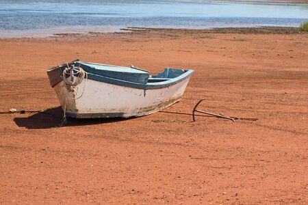 Un pequeño bote con su, por la que se ancla en una orilla de arena.  Foto de archivo - 3303353