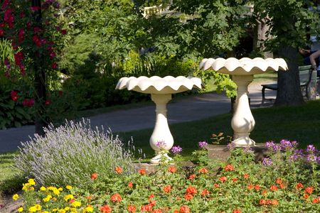 Two birdbaths side by side in a formal garden.