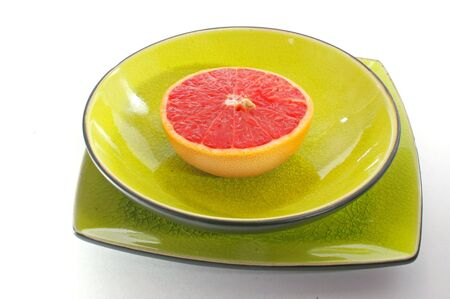 A pink fleshed grapefruit half served in yellow glazed dishware. Imagens - 3312185