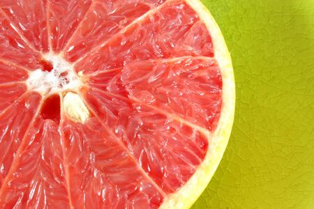 A pink fleshed grapefruit half served in yellow glazed dishware. Imagens