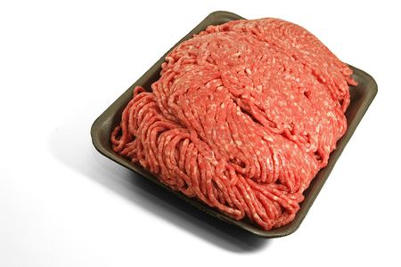 on the ground: Fresh ground beef on a styrofoam tray.