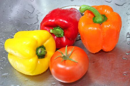 An array of freshly cleaned wet vegetables in a sink, including a variety of peppers and a tomato.