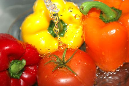 A variety of vegetables, including peppers and a tomato, in a stainless steel sink being washed under a stream of water.