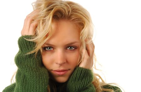 Beautiful blond model in green sweater on a white background with copyspace. Stock Photo