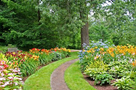 A path in a park running through beds of flowers, primarily daylilies. Stock Photo