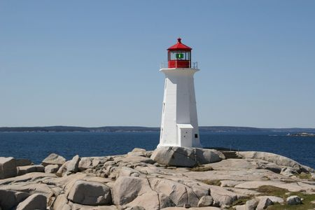 Rocks, ocean and lighthouse at Peggys Cove, Nova Scotia.