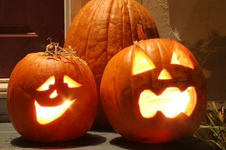 The carved faces of pumpkins glowing on Halloween.