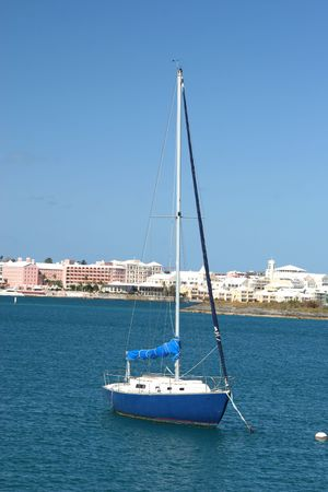hamilton: Sailboat in Hamilton Harbour, Bermuda with the city of Hamilton in the background.  Most notably the pink Hamilton Princess on the left.