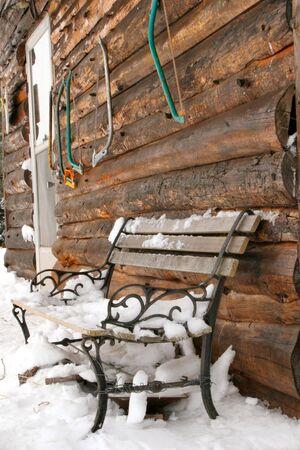 handsaw: A snowcovered banco en el porche delantero de una cabina r�stica de registro. Handsaws est�n en la pared.
