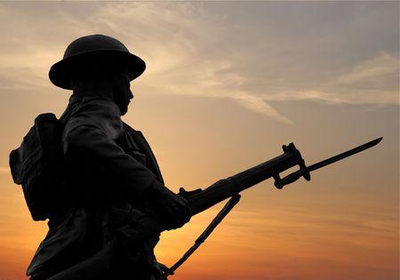 guerra: La silueta de un soldado WW1 cifra en un monumento de guerra contra un cielo del atardecer. Foto de archivo
