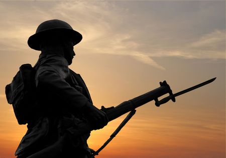against the war: The silhouette of a WW1 soldier figure in a war monument against a sunset sky.