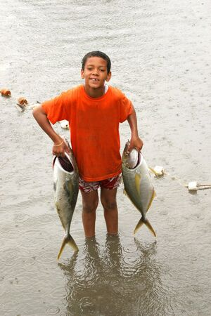 A young fisherman carrying part of his catch. photo