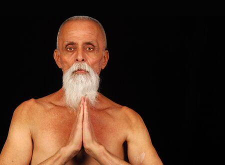 Senior man in traditional yoga pose.