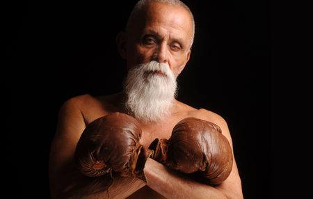 old people: A confident older boxer wearing old leather boxing gloves from the 30s.
