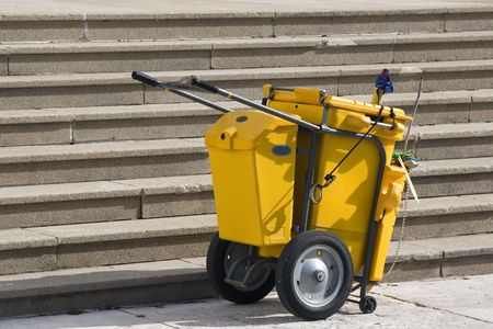 An industrial wheeled clean up cart or garbage can.  It has several compartments and some garbage hanging out of the front. Stock Photo - 4142021