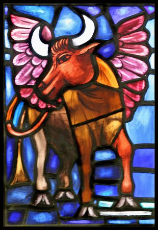 The winged ox is the evangelical symbol of St. Luke.  From an old stained glass window in an Anglican Church in Bermuda. Stock Photo - 4190733