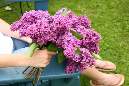 A bunch of lilac flowers held by a young woman. photo