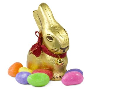 A golden chocolate Easter Bunny surrounded by candy eggs. photo