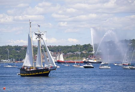 A tall ship is saluted with water canons as she sails out of Halifax Harbour with Dartmouth in the background photo