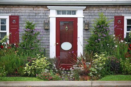fachada de casa: La entrada de una casa rodeada por arbustos de tejo y flores anuales y perennes.