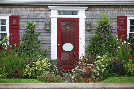 front of house: The entrance to a home surronded by yew shrubs and annual and perennial flowers.
