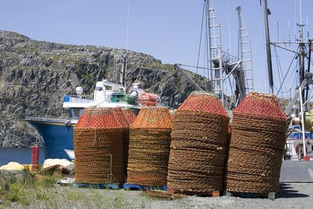 crab pots: Crab pots at the wharf in Cupids, Newfoundland, Canada.  A scallop dragger is docked behind them. Stock Photo
