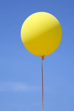 Yellow party ballon floating in mid air against a bright blue sky. Stock Photo