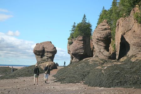Tourist walk at Hopewell Rocks, the famous Flower Pot Rocks of New Brunswick, Canada at low tide.