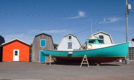 lobster boat: Commercial lobster boat outside colorful bait sheds prior to launching in the water in the spring.