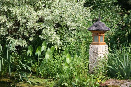 influenced: An Asian influenced garden lantern in an informal garden. Stock Photo
