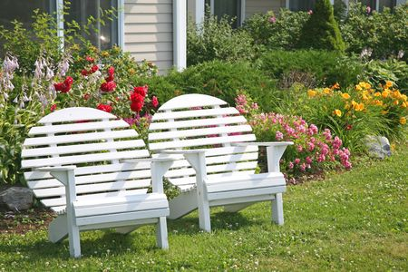 back yard: A round back Adirondack chair fondly know as a moon chair in front of a home and flower beds. Stock Photo