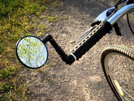 A rear view mirror of a bicycle pointed towards the treetops and sky.
