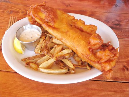 A plate of fish and chips with tarter sauce on a wooden table. Stock Photo - 7347569