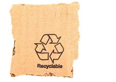 ripped: A recycle symbol printed on a ripped piece of cardboard.