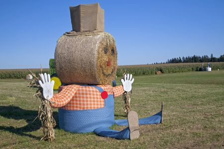 A giant Halloween scarecrow made out of stawbales in a farm setting.
