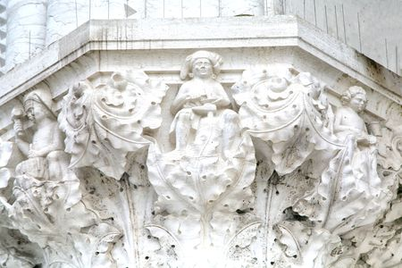 lavishly: The lavishly decorated capital at the top of an old marble column in the city of Venice, Italy.  The figure in the center is a shoemaker at work.