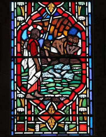 Stained glass window with fishermen disciples hauling in their nets full of fish. Stock Photo