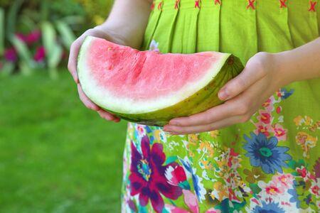 Een vrouw in een tropische jurk buiten in een tuin met een groot deel van watermeloen.