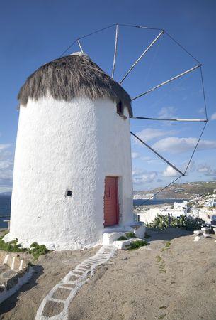 Windmill overlooking a village on the island of Mykonos, Greece. Stock Photo - 7894852