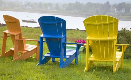 adirondack chair: Wooden Adirondack chairs positioned with a view of the river. Stock Photo