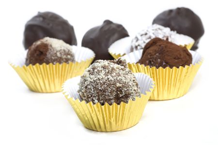 Homemade chocolate truffles with a variety of toppings such as cocoa, coconut, ground almonds.  Each sitting in a gold foil cup.